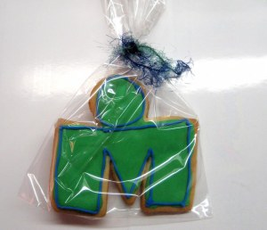 Photo of green and blue Ironman cookie, the m dot.