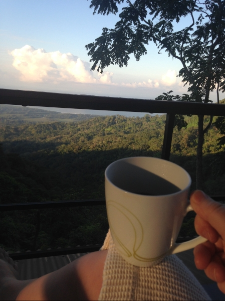 Enjoying coffee in a mug on balcony overlooking rain forest in Costa Rica.