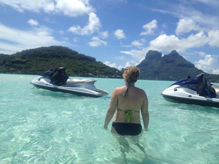 woman in ocean next to two jet skis