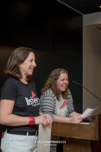 Two women in Listen To Your Mother T-shirts at podium laughing