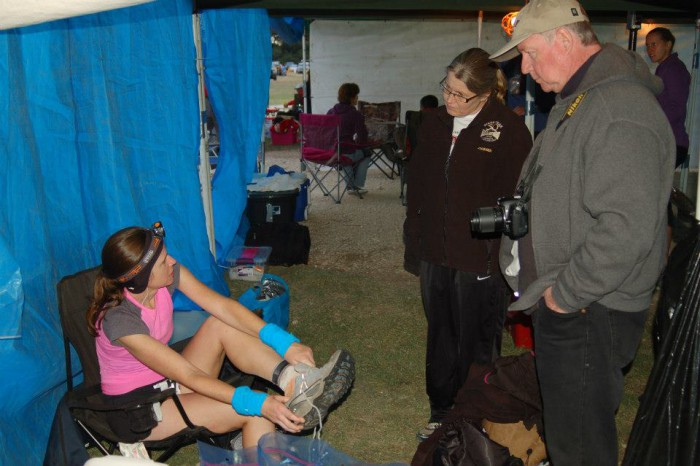 Trail runner at the aid station talks with support crew.