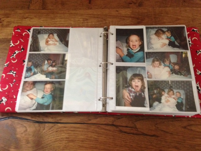Baby album open to pages showing family visit to the hospital and new baby.