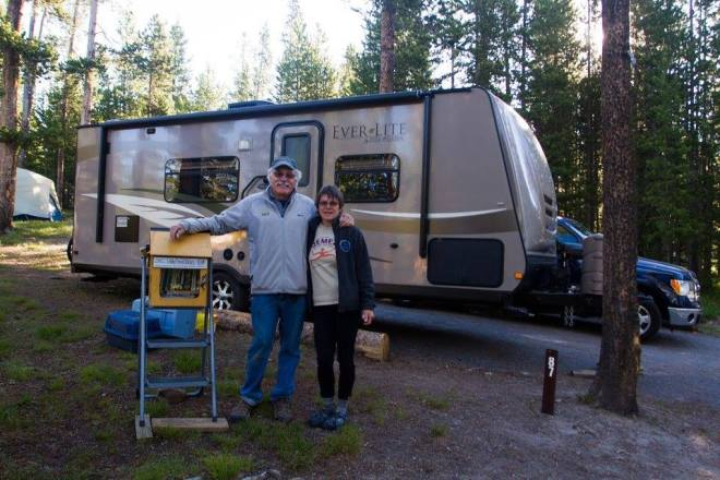 Couple with traveling Little Free Library at Yellowstone National Park