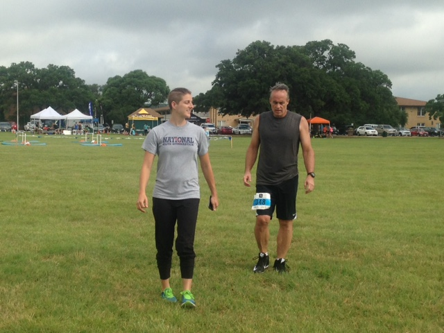 Trainer and athlete walk at event.