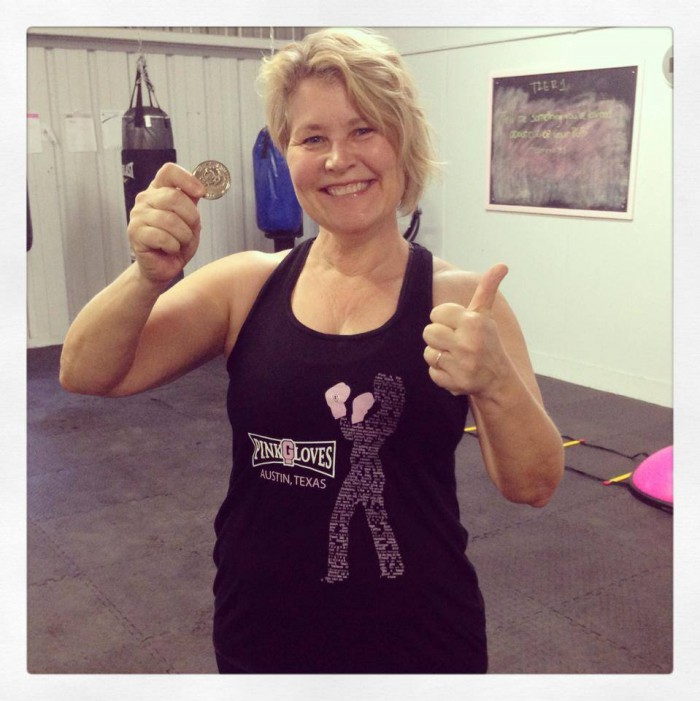 Leah Nyfeler holds up Pink Gloves Boxing Challenge Coin