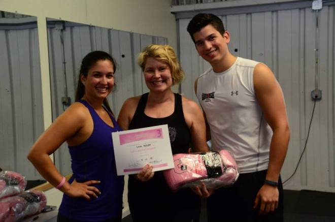 Boxing trainers with proud student, holding certificate