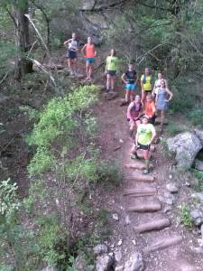 Women runners on hilly trail.