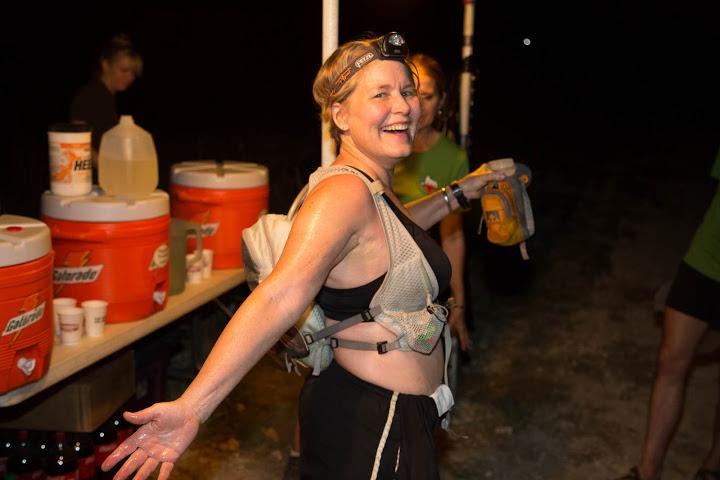 Sweaty female runner at nighttime trail race.