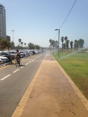 Cyclist rides through sprinkler spray on promenade near Charles Clore Park in Tel Aviv.