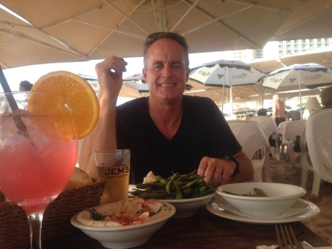 Man enjoying hummus, edamame, and cocktail.