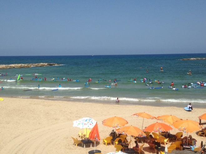 Beach umbrellas and surfers at Dolphinarium Beach in Tel Aviv .