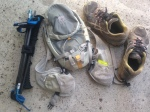 Folded trekking poles are next to backpack and shoes for size comparison.