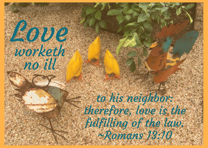 Metal chickens in a yard with quotation from Romans 13:10, Love worketh no ill to his neighbor: therefore, love is the fulfilling of the law.