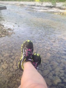 Photo of feet in trail shoes resting in a creek