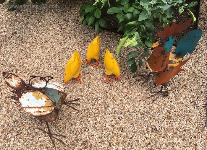 Five metal chickens in a garden