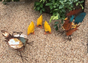 Five metal chickens in a garden