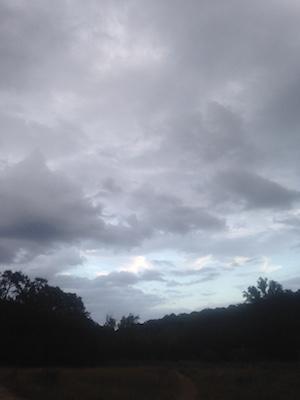 Storm clouds highlight Barton Creek greenbelt at dusk.