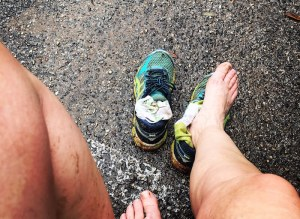 Photo of runner's dirty legs and feet after taking off shoes.