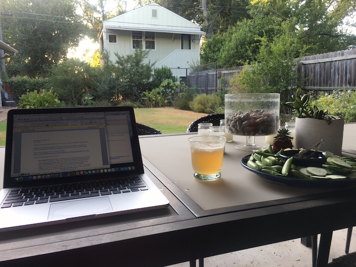 View of laptop, cocktail, and snack tray on table looking across backyard writing office.