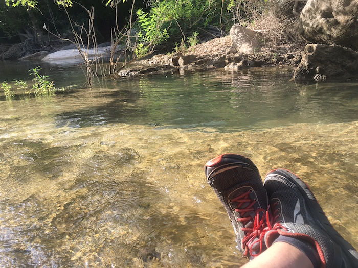 Scene of trail runner's shoes with beautiful Barton Creek in the background.