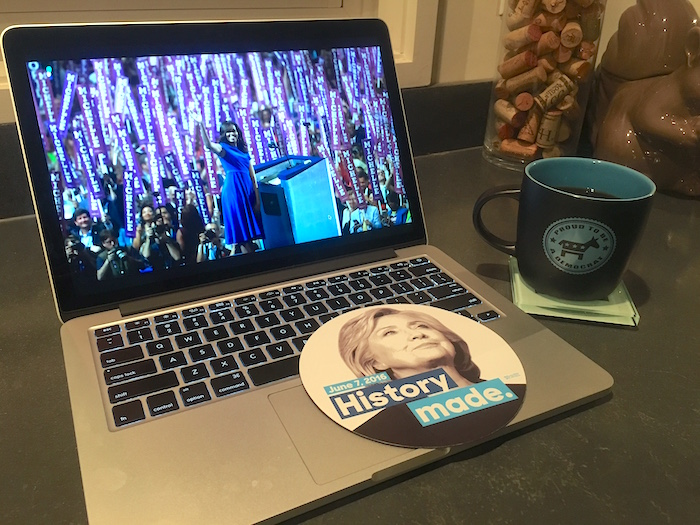 Computer showing Michelle Obama at 2016 DNC with Hillary Clinton button and democratic coffee mug.