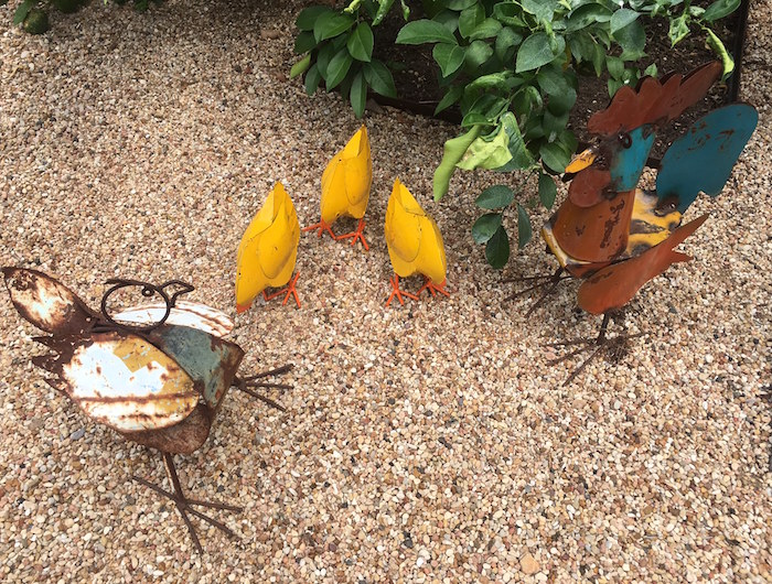 Hen, rooster, and three yellow chickens in metal yard art.