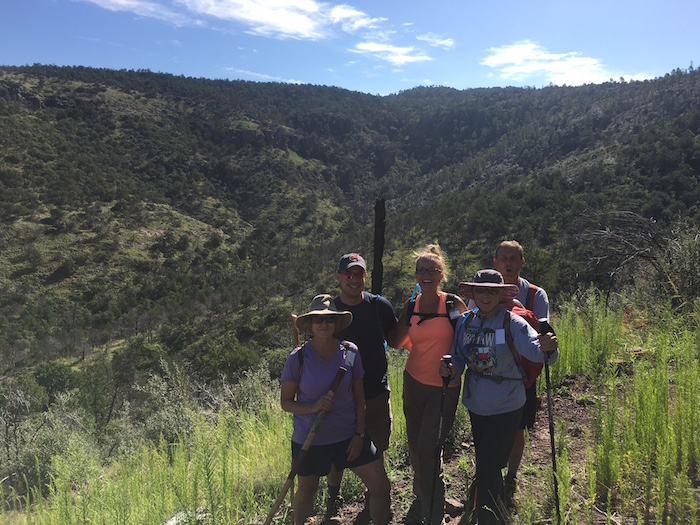 Four hikers on Wolf Den Canyon Trail in Davis Mountain Preserve.