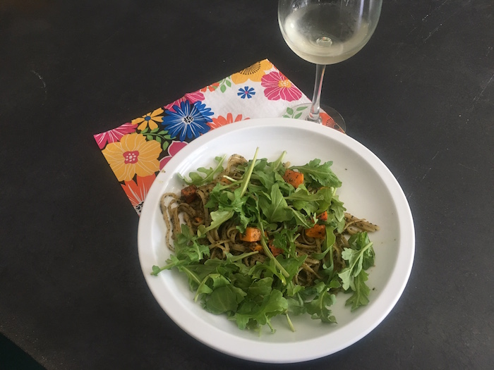 Plate of gluten free pasta with arugula and glass of wine.