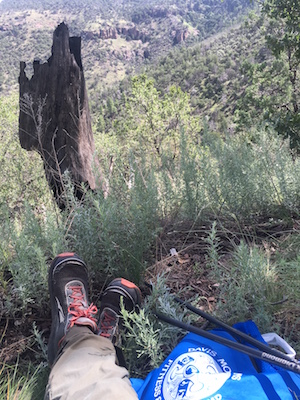 View of Wolf Den Canyon with hiker's shoes, bag, and trekking poles in foreground.