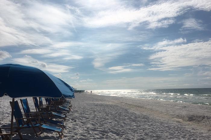 Empty beach chairs lining shore at Miramar Beach in September.