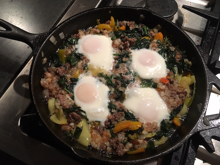 Cast iron skillet with sweet potato greens hash and cooked eggs.
