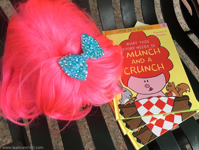 "Bright pink wig with sparkle bow next to copies of children's book ""What This Story Needs is a Munch and a Crunch"""