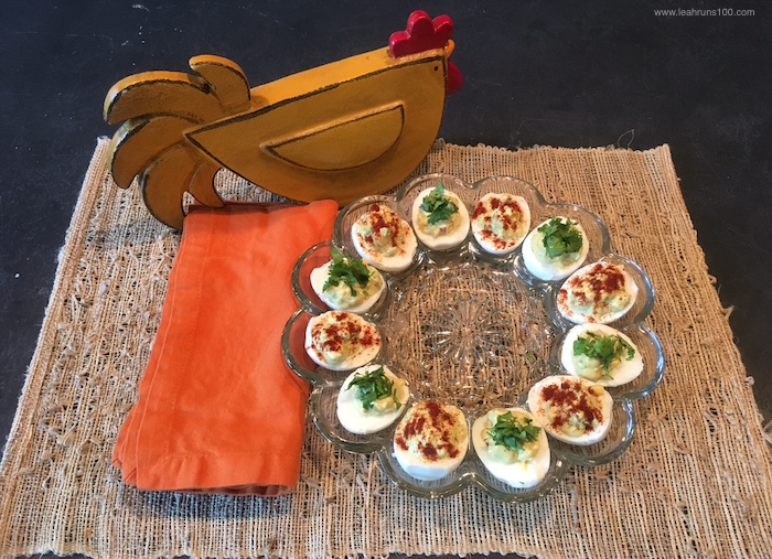 Deviled eggs on plate with wooden chicken.