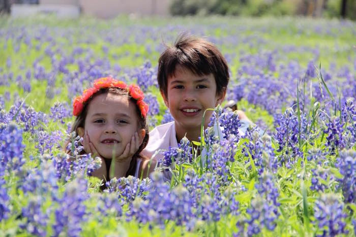 Two kids nestled in a field of blooming bluebonnets in Round Rock, TX
