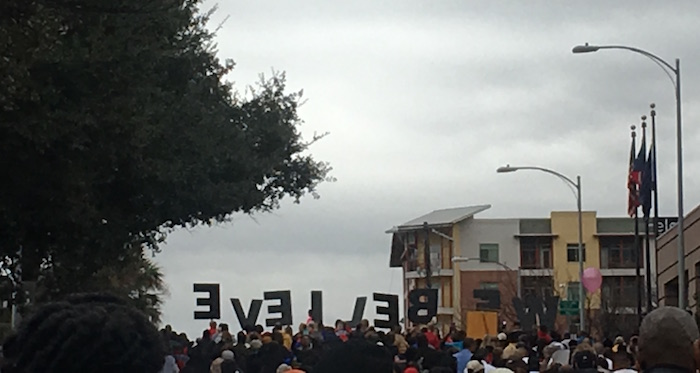 "Austin's MLK Day March crests hill with sign spelling out ""We Believe."""