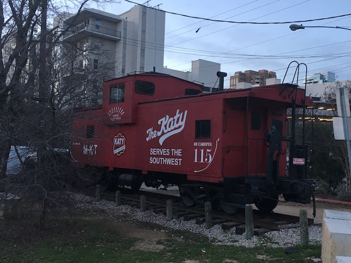 "Red caboose with ""The Katy"" painted on side, located next to Katy Trails Icehouse"