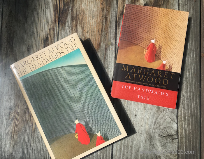 Paperback and hardback copies of The Handmaid's Tale by Margaret Atwood on wooden background