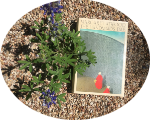 1986 hardback copy of Margaret Atwood's The Handmaid's Tale next to bluebonnets