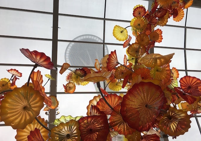 Giant orange glass sculpture on ceiling at Chihuly Garden and Glass Museum frames view of Seattle Space Needle