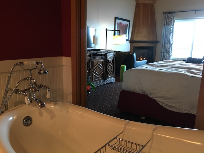 Room at Edgewater Hotel showing clawfoot tub, fireplace and window.