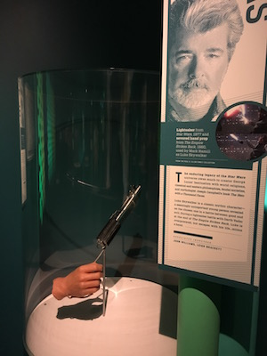 George Lucas information with hand and light saber prop from Star Wars movie.
