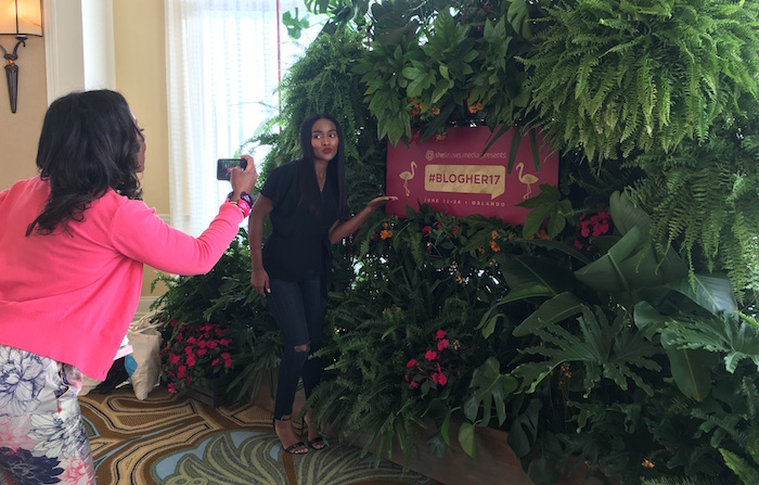 Two women taking photos with BlogHer 2017 sign and greenery.