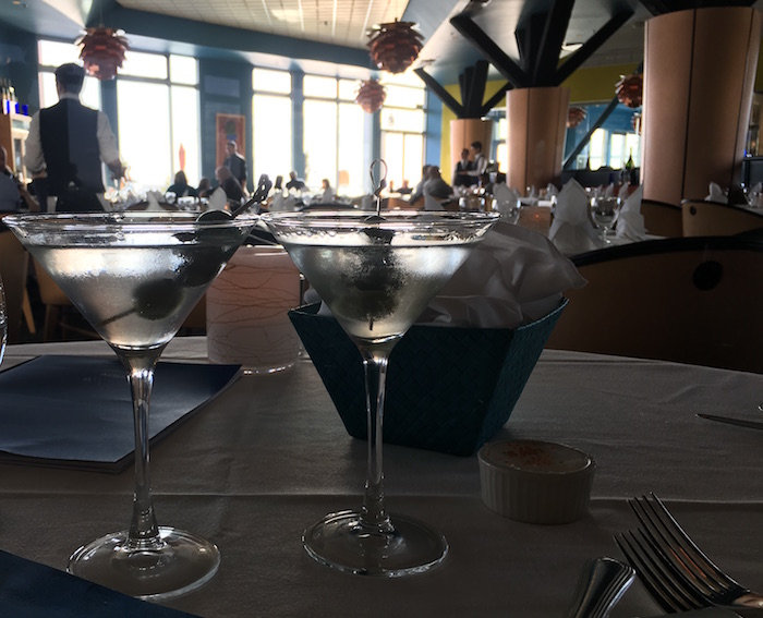 Two martinis on the table at Aqua in Seattle and looking across to windows.